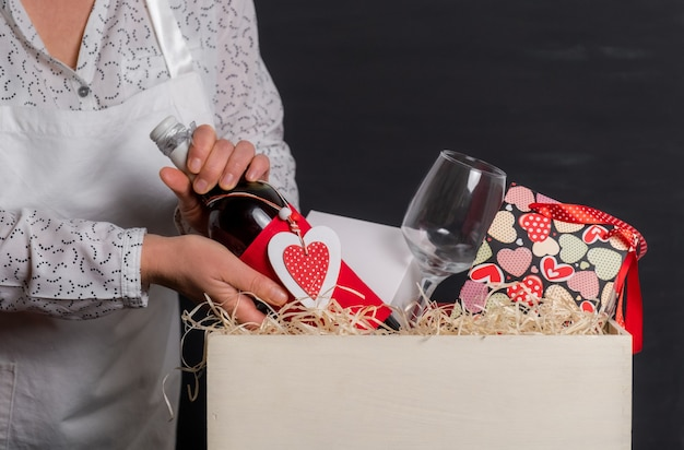 Deliver puts wine bottle with red heart of valentine's day in white box with festive bag and wineglasses