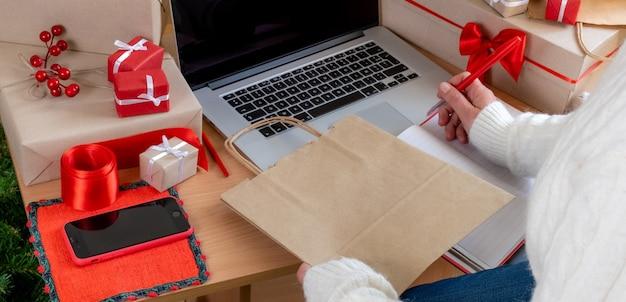 포장 가방 및 선물 상자 근처에서 노트북을 사용하여 배달의 손.