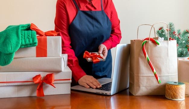 パッキングバッグ、ギフトボックス、クリスマスツリーの近くでノートパソコンを使用して手を届けます。オンライン配信の概念。