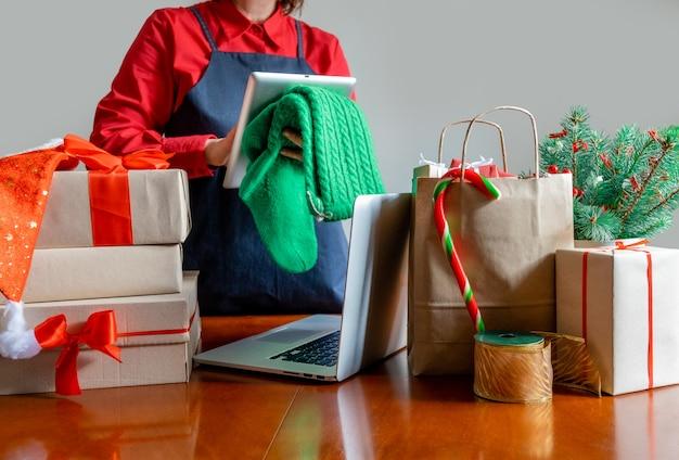ラップトップ、パッキングバッグ、ギフトボックス、クリスマスツリーの近くでタブレットを使用して手を届けます。オンライン配信の概念。