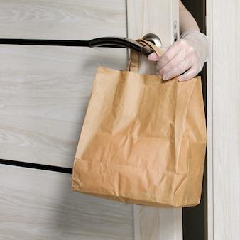 Доставка еды в бумажном пакете во время вспышки covid 19. женская рука берет продуктовый пакет у входной двери. пожертвование, концепция карантина.