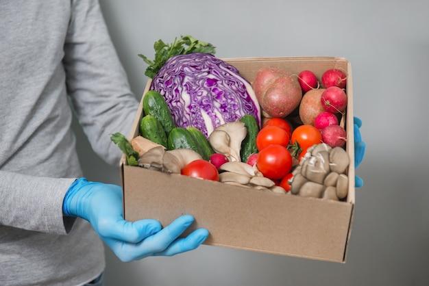 コロナウイルス検疫中に安全な手袋をはめた紙箱に新鮮な野菜を届ける