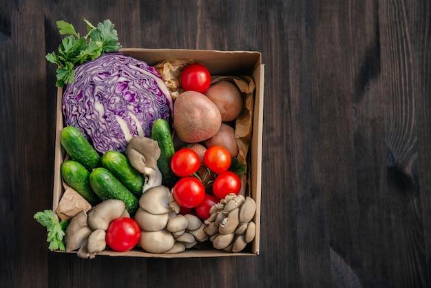 新鮮な野菜を紙箱に入れてお届けします。木の背景に健康的なベジタリアン料理の上面図