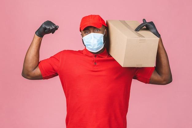 Доставка афро-американский мужчина в красной кепке пустая футболка униформа маска для лица перчатки держат пустую картонную коробку