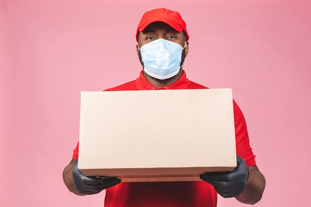 Delivery african american man employee in red cap blank t-shirt uniform face mask gloves hold empty cardboard box