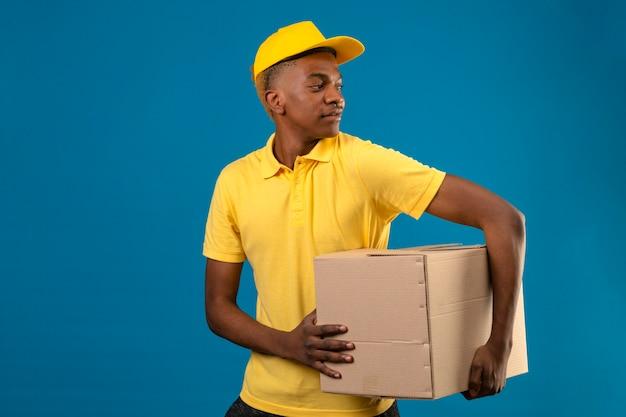 Афро-американский мужчина доставки в желтой рубашке поло и кепке держит картонные коробки, глядя в сторону с улыбкой на лице, стоя на синем
