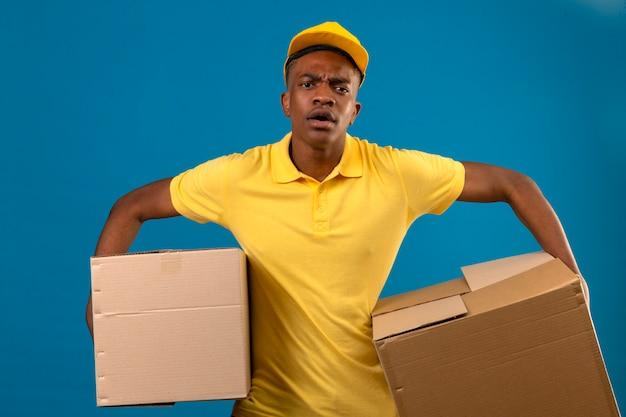 Афро-американский мужчина-доставщик в желтой рубашке поло и кепке держит картонные коробки, выглядит потрясенным, потрясенным, с удивленным лицом, сердитым и расстроенным, стоя на изолированном синем