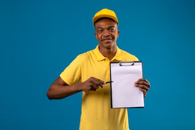 Афро-американский мужчина доставки в желтой рубашке поло и кепке держит буфер обмена с пробелами, указывающими на него ручкой, дружелюбно улыбаясь, стоя на синем