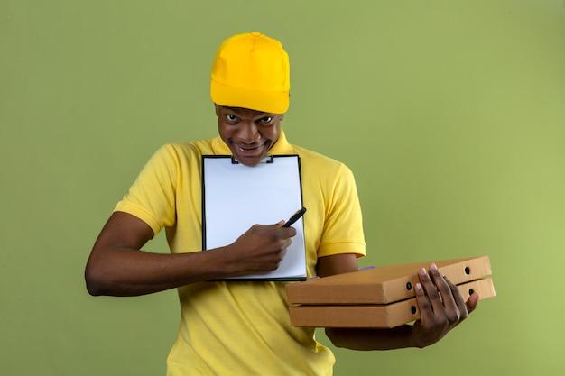 Афро-американский мужчина-доставщик в желтой рубашке поло и кепке держит коробки для пиццы и буфер обмена с просьбой подписать, стоя на изолированном зеленом
