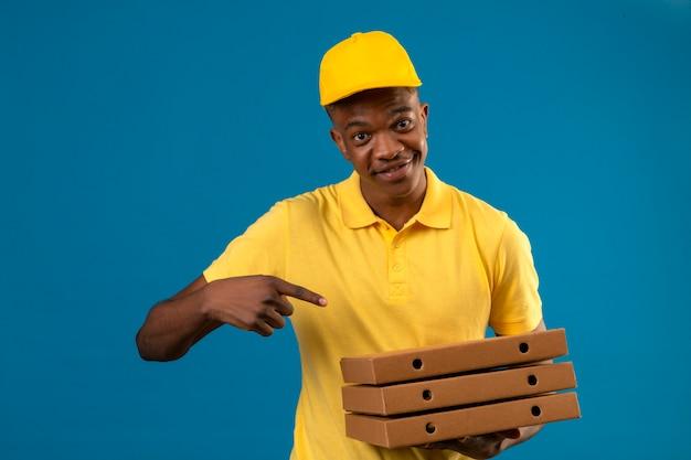 Афро-американский мужчина-доставщик в желтой рубашке поло и кепке держит коробки для пиццы и показывает пальцем на них, дружелюбно улыбаясь, стоя на изолированном синем
