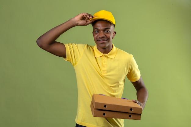 Афро-американский мужчина доставки в желтой рубашке поло и кепке держит коробки для пиццы, приветствуя трогательно его кепку, дружелюбно улыбаясь, стоя на зеленом