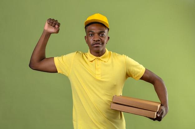 黄色のポロシャツとピザの箱を持ってアフリカ系アメリカ人の配達人は自信を持って彼の拳を握りしめながら自信を持って彼の拳を握りしめ、彼の目的と目標を達成するために緑色で立っています。