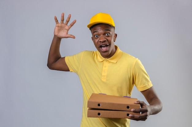 Афро-американский мужчина доставки в желтой рубашке поло и кепке держит коробки для пиццы, выглядя возбужденными и удивленными, стоя с поднятой рукой