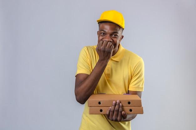 Афро-американский мужчина-доставщик в желтой рубашке поло и кепке держит коробки с пиццей, радостно грызет ногти в ожидании сюрприза