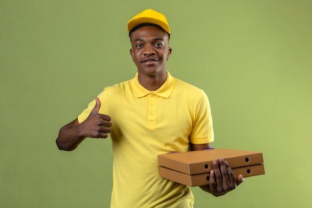 Афро-американский мужчина доставки в желтой рубашке поло и кепке держит коробки для пиццы, указывая в сторону с большим пальцем и весело улыбаясь, стоя на изолированном зеленом