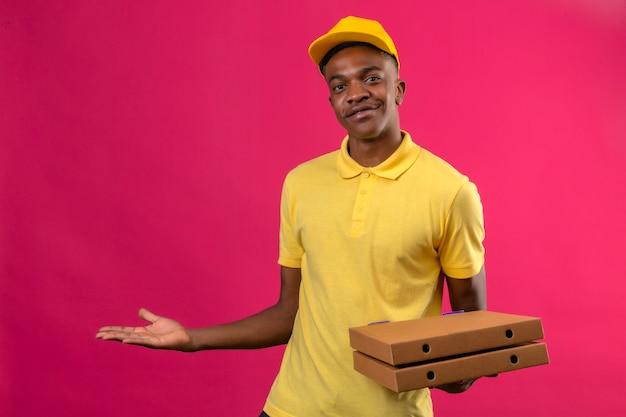Афро-американский мужчина доставки в желтой рубашке поло и кепке держит коробки для пиццы, представляя и указывая ладонью руки, стоящей на изолированном розовом