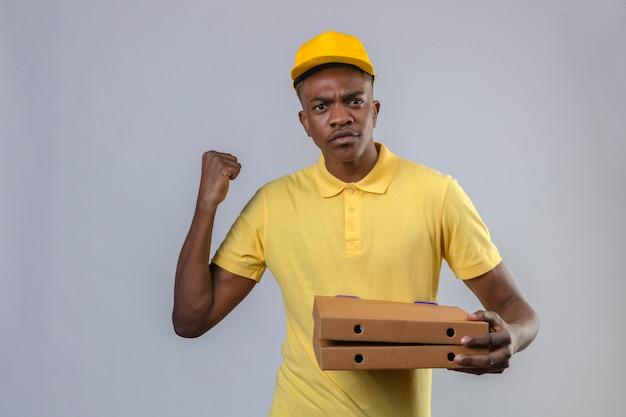 Афро-американский мужчина-доставщик в желтой рубашке поло и кепке держит коробки для пиццы, поднимая кулак с сердитым выражением лица, угрожающим стоя