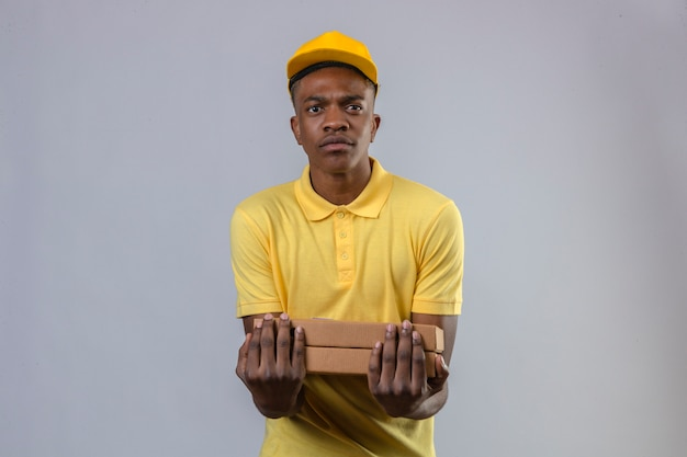 Афро-американский мужчина доставки в желтой рубашке поло и кепке держит коробки для пиццы с нахмуренным лицом