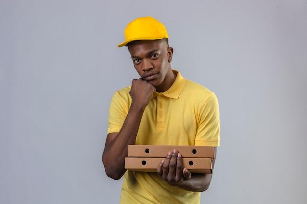 Афро-американский мужчина доставки в желтой рубашке поло и кепке, держащий коробки для пиццы с рукой на подбородке, ждет с серьезным лицом