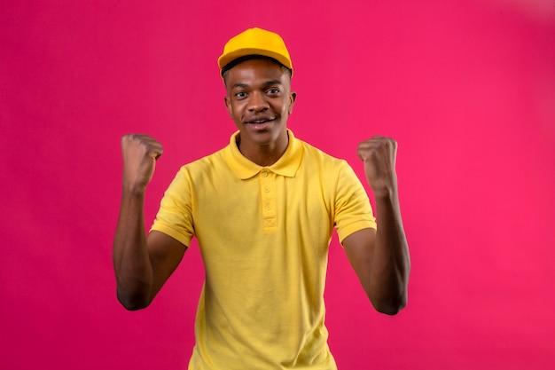 黄色のポロシャツとキャップを探しているアフリカ系アメリカ人の配達人は、彼の成功と喜びと彼の拳を握り締めて勝利し、ピンクの上に立って彼の目的と目標を達成した
