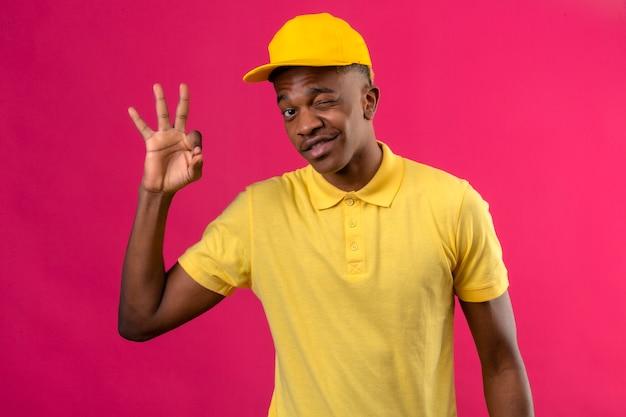 黄色のポロシャツとピンクのokサインを行うウインクうれしそうなウインクを探してキャップでアフリカ系アメリカ人の配達