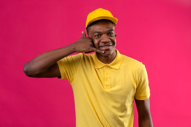 黄色のポロシャツとキャップ作るアフリカ系アメリカ人の配達のジェスチャーはピンクに元気に笑顔で自信を持ってジェスチャーを呼び出す