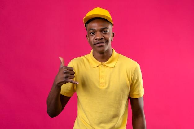 黄色のポロシャツとキャップ作るアフリカ系アメリカ人の配達のジェスチャーはピンクに優しい笑顔で自信を持ってジェスチャーを呼び出す