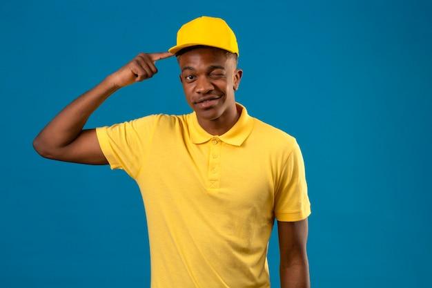黄色のポロシャツとキャップポインティングテンプルウインクブルーにうれしそうな立っているを探してアフリカ系アメリカ人の配達人