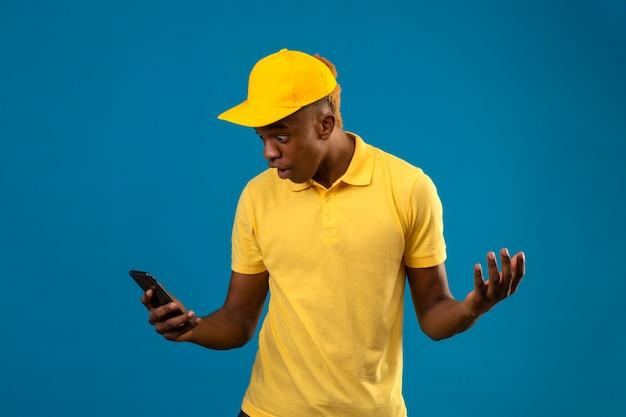 黄色のポロシャツとキャップでアフリカ系アメリカ人の配達人は画面を見てショックを受けて広がる手のひらああ分離された青の上に立って彼の携帯電話