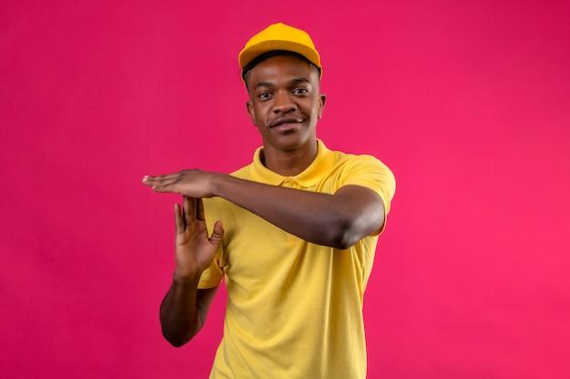 Афро-американский мужчина доставки в желтой рубашке поло и кепке улыбается, делая жест тайм-аута на розовом