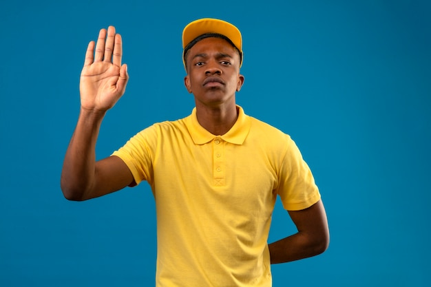 Афро-американский мужчина доставки в желтой рубашке поло и кепке, стоящий с открытой рукой, делает знак остановки с серьезным и уверенным жестом защиты на изолированном синем