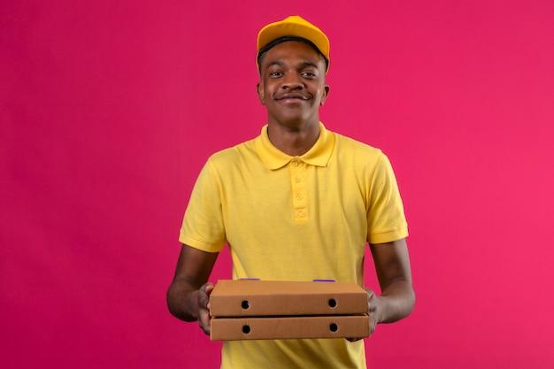 黄色のポロシャツとピンクのフレンドリーな笑顔の手でピザの箱で立っているキャップでアフリカ系アメリカ人の配達人