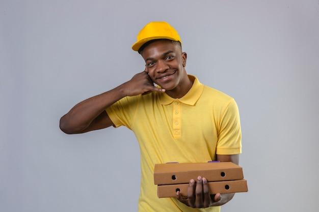 黄色のポロシャツとピザの箱に立っているキャップでアフリカ系アメリカ人の配達は私に自信を持って笑顔のフレンドリーな探しているジェスチャーを呼んで