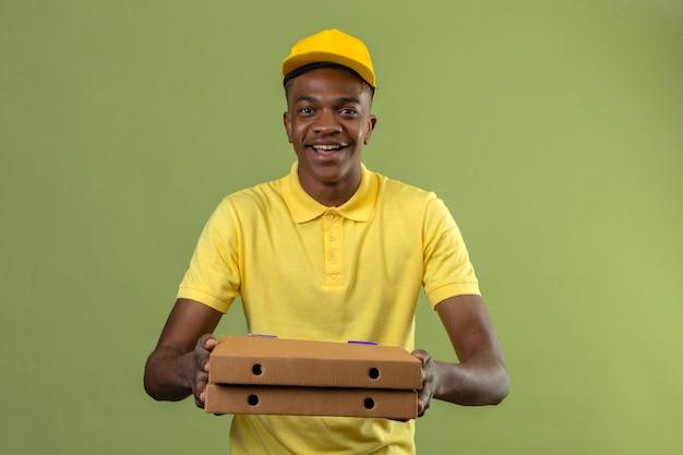 Афро-американский мужчина доставки в желтой рубашке поло и кепке, стоящий с коробками для пиццы, дружелюбно улыбаясь, со счастливым лицом, стоящим на зеленом