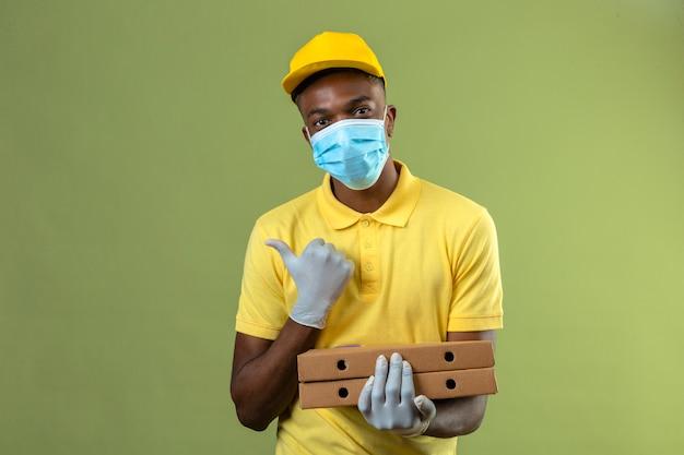 노란색 폴로 셔츠와 모자 녹색에 엄지 손가락으로 측면을 가리키는 얼굴에 미소로 피자 상자를 들고 의료 보호 마스크를 쓰고 배달 아프리카 계 미국인 남자