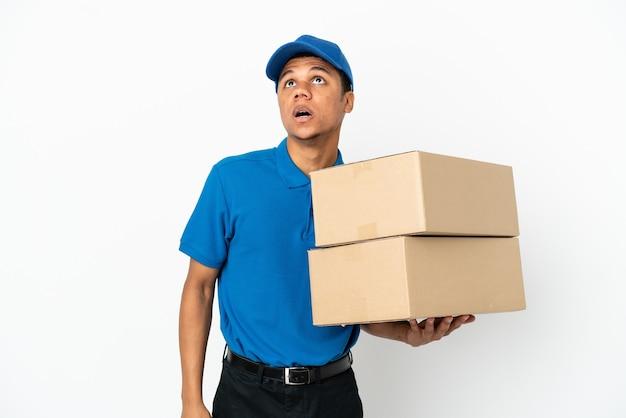 Афро-американский мужчина доставки, изолированные на белом фоне, глядя вверх и с удивленным выражением лица