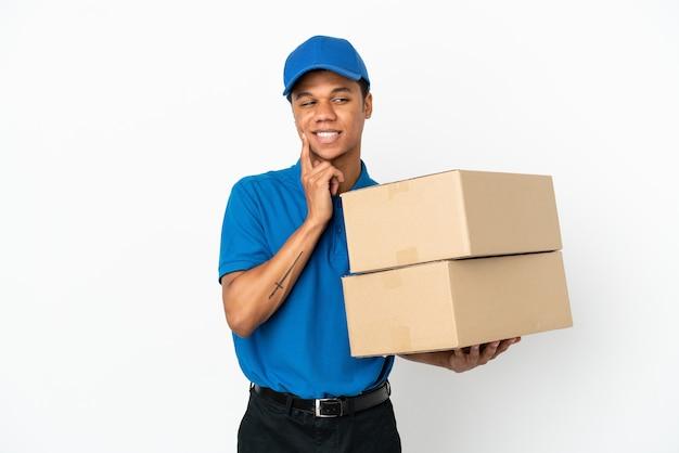 Афро-американский мужчина доставки, изолированные на белом фоне, думает о идее, глядя вверх