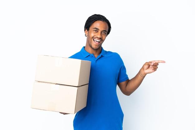 Доставка афро-американский мужчина с косами на белом, указывая пальцем в сторону и представляя продукт