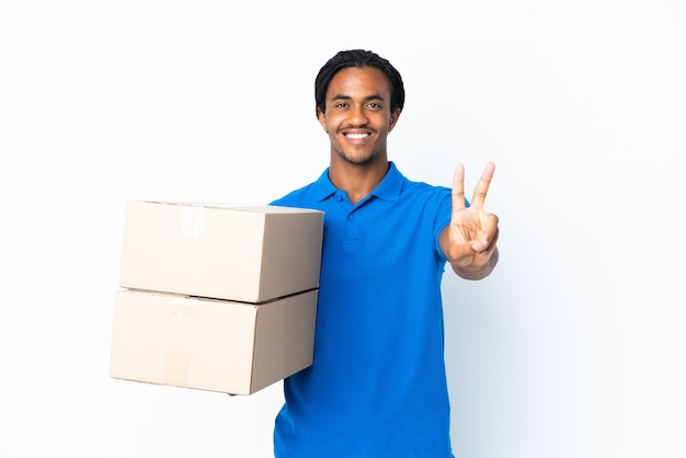 Delivery african american man with braids on white smiling and showing victory sign