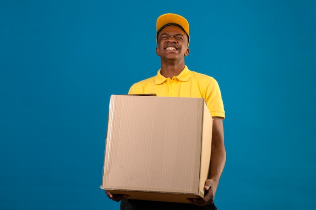 Delivery african american man in yellow polo shirt and cap holding big heavy cardboard box feeling unwell because of heavy weight on blue