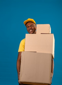 Delivery african american man in yellow polo shirt and cap holding big heavy cardboard boxes feeling unwell because of heavy weight on blue