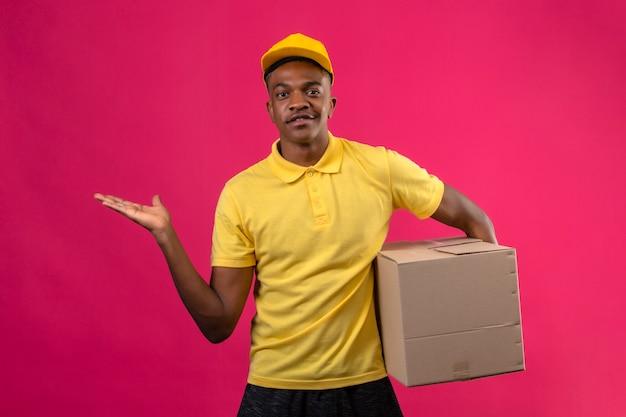 Consegna uomo afroamericano in camicia di polo gialla e berretto che tiene il pacchetto della scatola che presenta e che indica con il palmo della mano in piedi sul rosa isolato