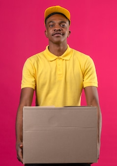 Consegna uomo afroamericano in maglietta polo gialla e berretto tenendo la scatola di cartone guardando fiducioso in piedi sul rosa
