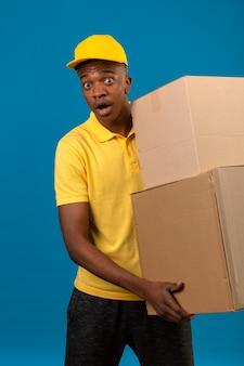 Consegna uomo afroamericano in maglietta polo gialla e berretto che tiene scatole di cartone scioccato con faccia sorpresa in piedi sul blu isolato