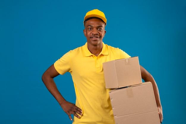 Consegna uomo afroamericano in maglietta polo gialla e berretto tenendo le scatole di cartone con un sorriso amichevole in piedi sul blu isolato