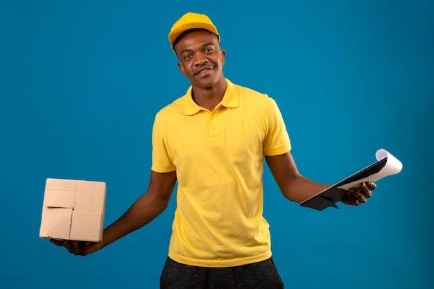 Uomo afroamericano di consegna in camicia di polo gialla e cappuccio che tiene appunti e scatola di cartone con un sorriso sicuro in piedi sul blu isolato