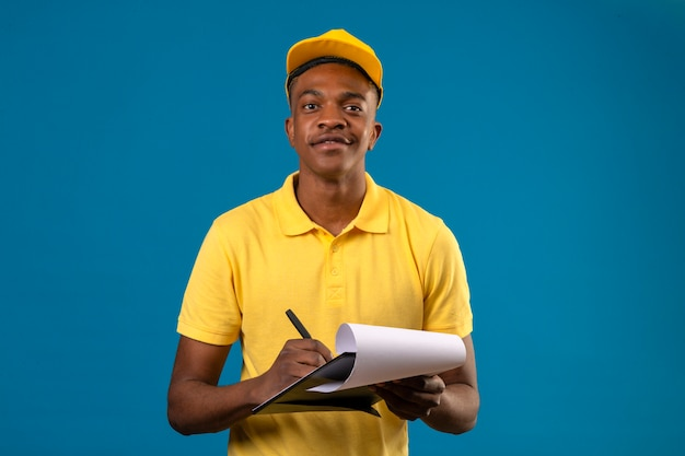 Delivery african american man in yellow polo shirt and cap holding clipboard writing something looking confident and proud standing on isolated blue