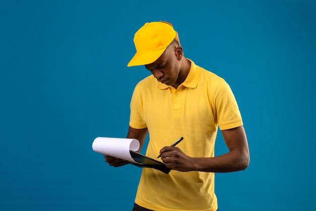 Uomo afroamericano di consegna in camicia di polo gialla e cappuccio che tiene appunti scrivendo qualcosa con la faccia seria che sta sul blu isolato