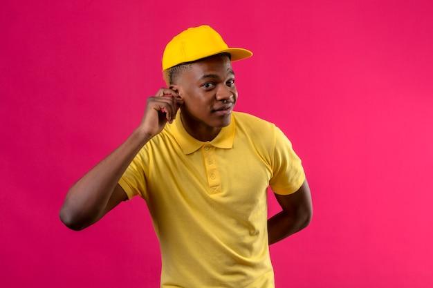 Consegna uomo afroamericano in polo gialla e berretto tenendo la mano vicino al suo orecchio cercando di ascoltare la conversazione di qualcuno in piedi sul rosa