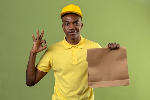 Uomo afroamericano di consegna in camicia di polo gialla e cappuccio che tiene il pacchetto di carta che sembra sorridente allegro che fa segno giusto sul verde